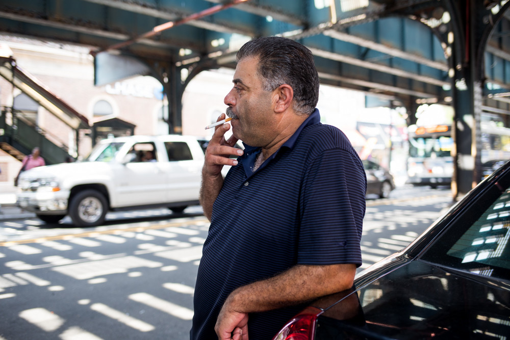 Cab driver Suveh Awad takes a drag on a cigarette as he leans on his car at West 231st Street and Broadway. A driver for 12 years, Awad disagrees with the notion that the cap on Uber- and Lyft-style vehicles Mayor Bill de Blasio signed into law Aug. 14 will alleviate congestion in the city. He blames bus and bike lanes that create narrower streets.