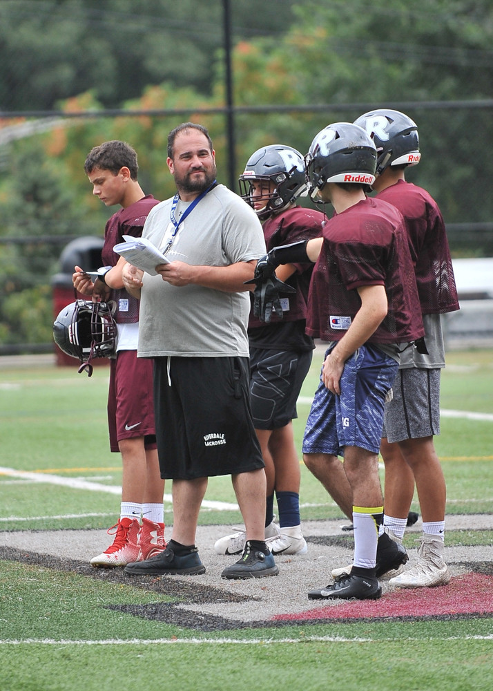 Riverdale Country School head coach Joe Otero looks over his new group of players as he prepares the Falcons for the upcoming season, which kicks off Sept. 8 versus Horace Mann.