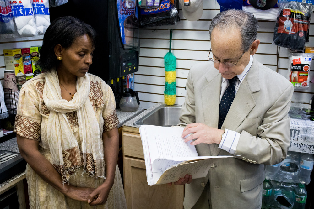 Attorney Jerald Kreppel looks through paperwork at Cool N Cozy near Jerome Avenue, a bodega owned by husband and wife Mulu Woldezghi and Ledetu Ghebremedhin of Sedgwick Avenue. A settlement with the city over the sale of an illegally priced cigar ultimately cost the bodega its license to sell tobacco.