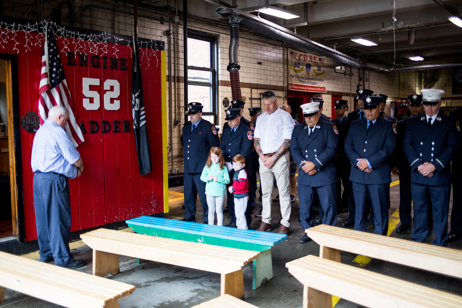 Ladder 52 firefighters stand for a moment of silence for those who died on Sept. 11, 2001, inside the firehouse while it rains heavily outside.