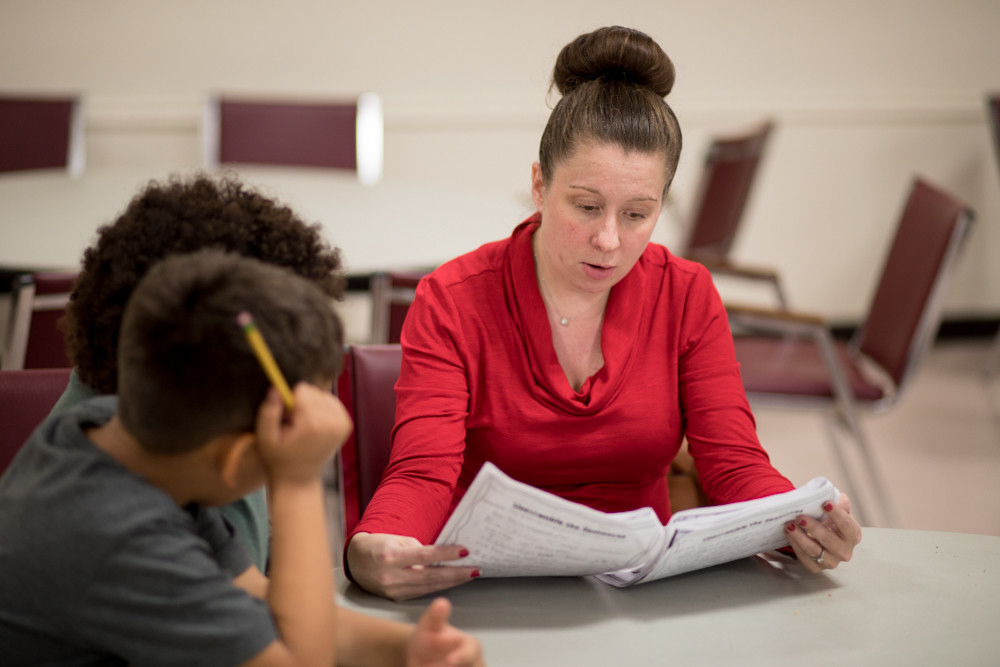 Michelle Bassolino, who works as a kindergarten teacher at P.S. 81, reviews the homework of two students in an after-school program at The Riverdale Y. The Y is one of the many after-school and tutoring programs that cater to Riverdale students.