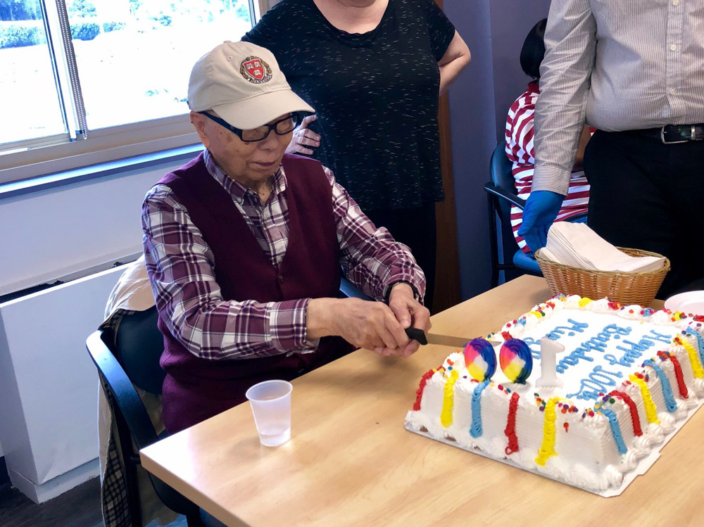 Ming Chin cuts into his birthday cake at Riverdale Senior Services. Chin, who celebrated his 100th birthday Aug. 27, suffers from Chin has early dementia and attends the adult day program for early memory loss at RSS nearly every week.