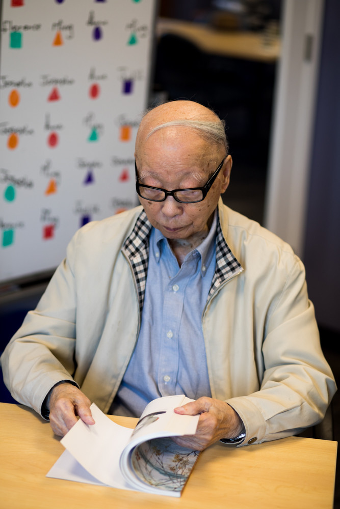 Ming Chin looks through a book of his late wife's paintings at Riverdale Senior Services. Chin, who celebrated his 100th birthday Aug. 27, raised two children and attends the adult day program for early memory loss at RSS nearly every week.