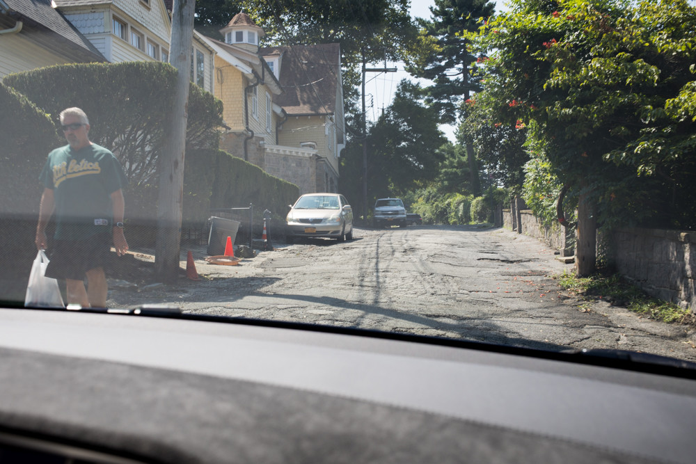 Sycamore Avenue, as seen from inside Teena Lerner's Tesla, has seen better days. The street is plagued with uneven pavement and cracked asphalt. Lerner just wants it repaved, but it's not so simple. A major part of the problem is figuring out who's responsible for fixing roads the city claims it doesn't own.