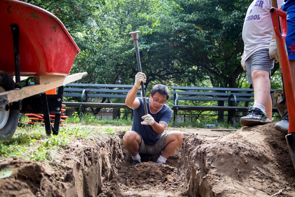 Xin Ye, a volunteer with the Stewards of Henry Hudson Park, uses a hoe to loosen soil in a plant bed at the park.