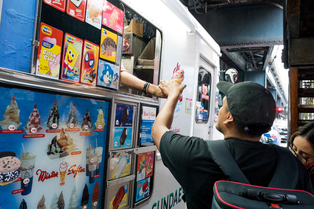 A Mister Softee driver, who identified himself as Victor Emmanuel, hands an ice cream cone to a customer on the corner of West 231st Street and Broadway. Since Emmanuel started driving three months ago, he's received a couple complaints about his truck's iconic jingle, although at this point it was barely audible over the roaring 1 train overhead and rush hour traffic.