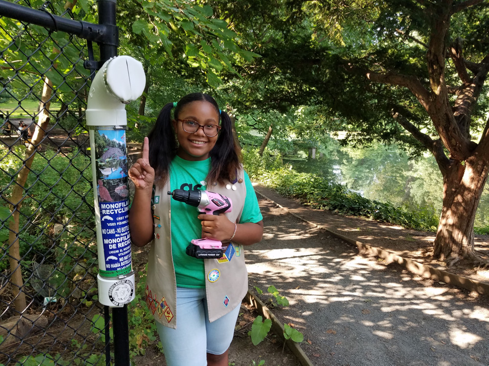 Karaugh-Nea Rodriguez smiles after successfully installing a fishing line receptacle in Van Cortlandt Park. Over the summer, Rodriguez, out of concern for the environment and as a Girl Scout, built and installed 12 fishing line receptacles across Van Cortlandt Park and Brooklyn's Floyd Bennett Field with the help of her father. The receptacles are places where fishermen can dispose their old line, without hurting animals.