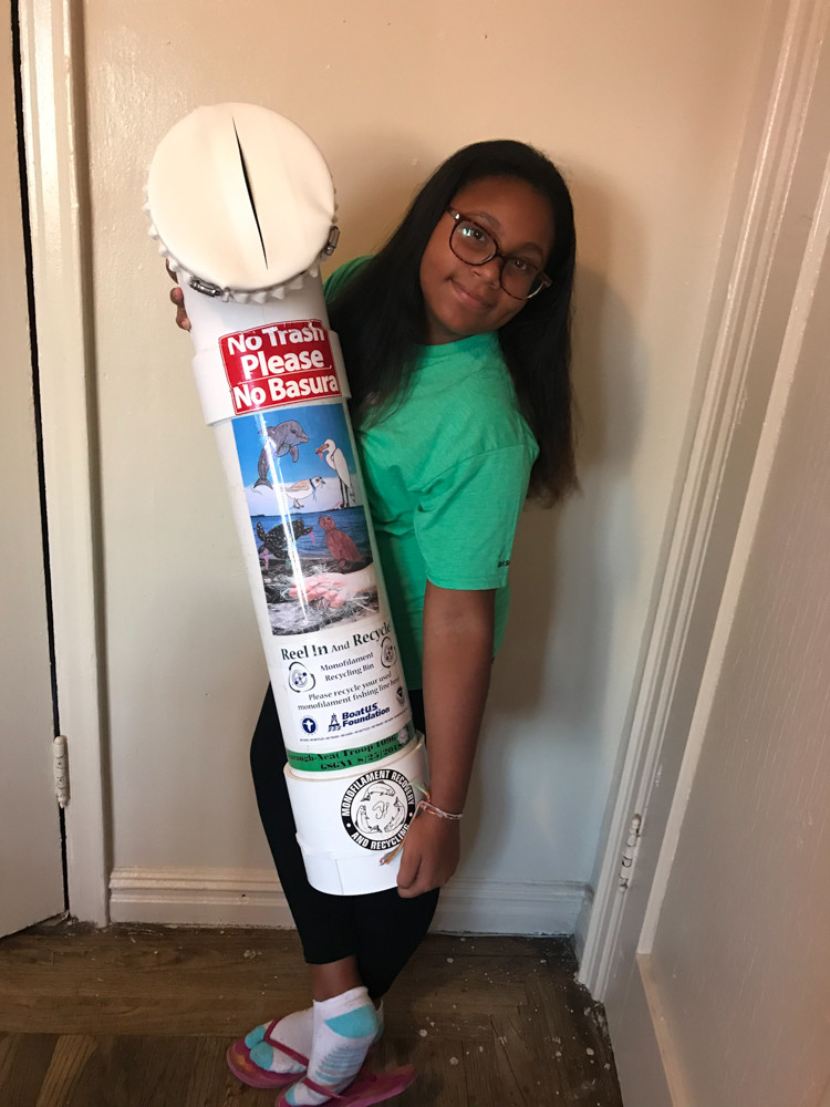 Karaugh-Nea Rodriguez holds a fishing line receptacle that she built with the help of her father. Over the summer, Rodriguez built and installed 12 fishing line receptacles across Van Cortlandt Park and Brooklyn's Floyd Bennett Field. The 11-year-old is a Girl Scout dedicated to helping preserve wildlife harmed by lines.