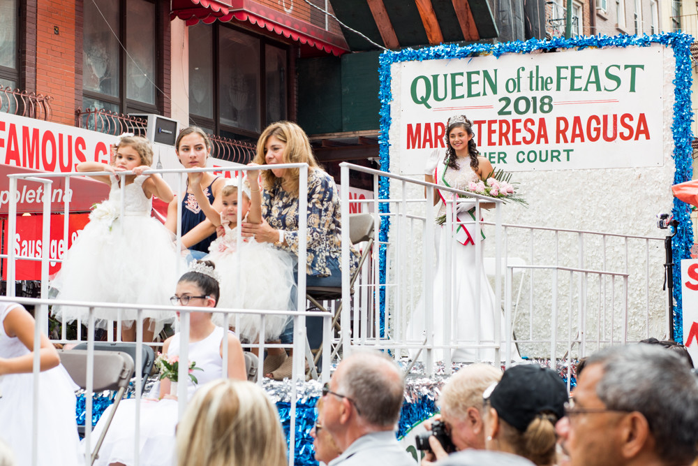 Marieteresa Porcher waves atop her float in the Feast of San Gennaro's grand procession. A Girl Scout and student at Riverdale/Kingsbridge Academy, Porcher was named this year's Queen of the Feast.