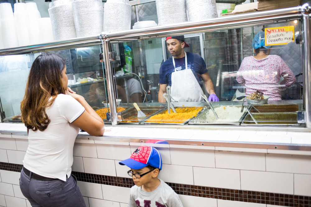 Jose Taveras takes a customer's order at the Taveras Food Center near West 225th Street in Marble Hill. The shop has been in business for at least 25 years, but rising rents and onerous taxes make survival a challenge.