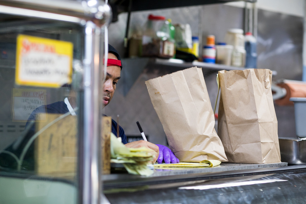 Manager Jose Taveras writes down a customer's food order at Taveras Food Center in Marble Hill. Obstacles like high rent and taxes make life hard for the city's small businesses, but Taveras and his tight-knit team have persisted for 25 years.