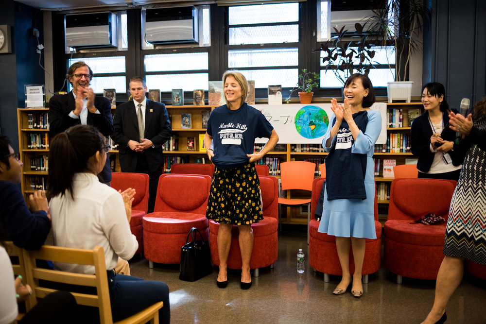 Caroline Kennedy, the former U.S. ambassador to Japan, puts on a gym shirt at the Marble Hill School for International Studies. Kennedy visited the school with Japanese first lady Akie Abe, second from right.