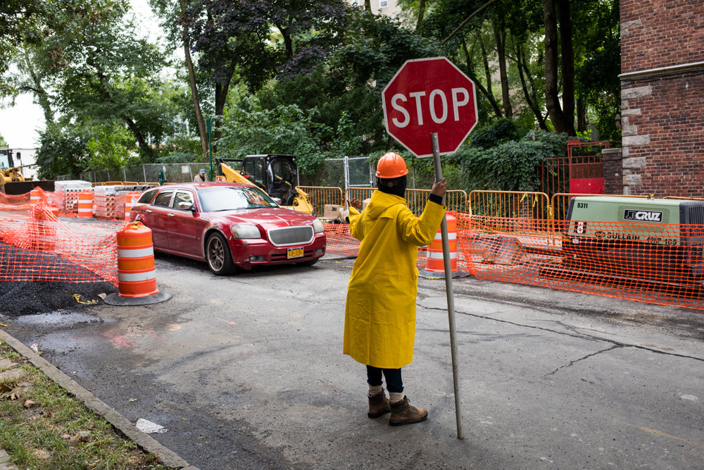 A car drives slowly along West 238th Street toward Johnson Avenue where ongoing gas line repair work by Con Edison has caused headaches for motorists in the area. Work began after the city's transportation department paved streets in the area recently.