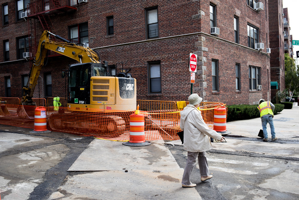 A pedestrian crosses West 238th Street along Johnson Avenue where ongoing gas line repair work by Con Edison has caused headaches for motorists. The street is under what seems to be constant repair due to the city transportation department's longstanding issue of poor communication with other agencies.