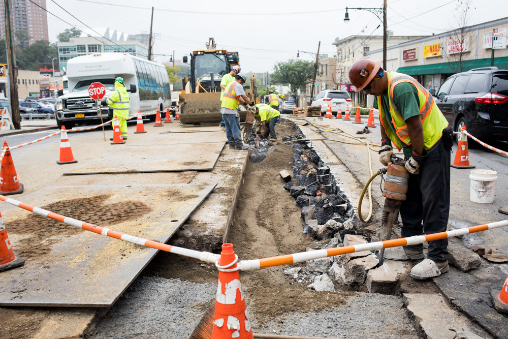 A repair worker uses a jackhammer on asphalt on Riverdale Avenue between West 256th and West 259th streets. The work creates a bottleneck along the avenue that slows traffic significantly.