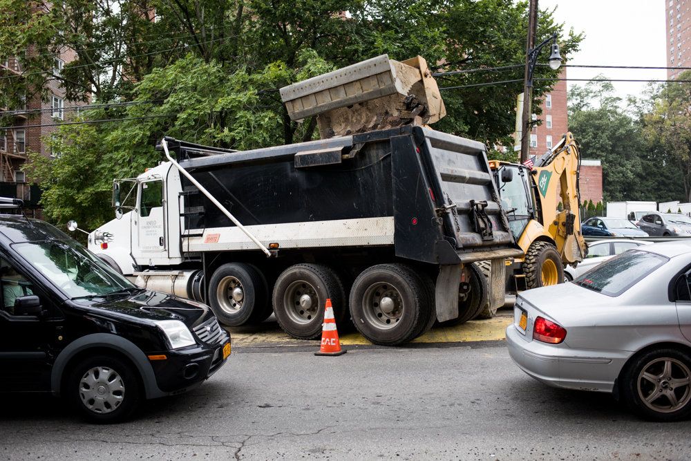 A backhoe loader drops debris into a dump truck on Riverdale Avenue. The transportation department is responsible for repaving roads and issuing permits for street work. Sometimes newly repaved streets are opened shortly after due to disorganized planned roadwork.