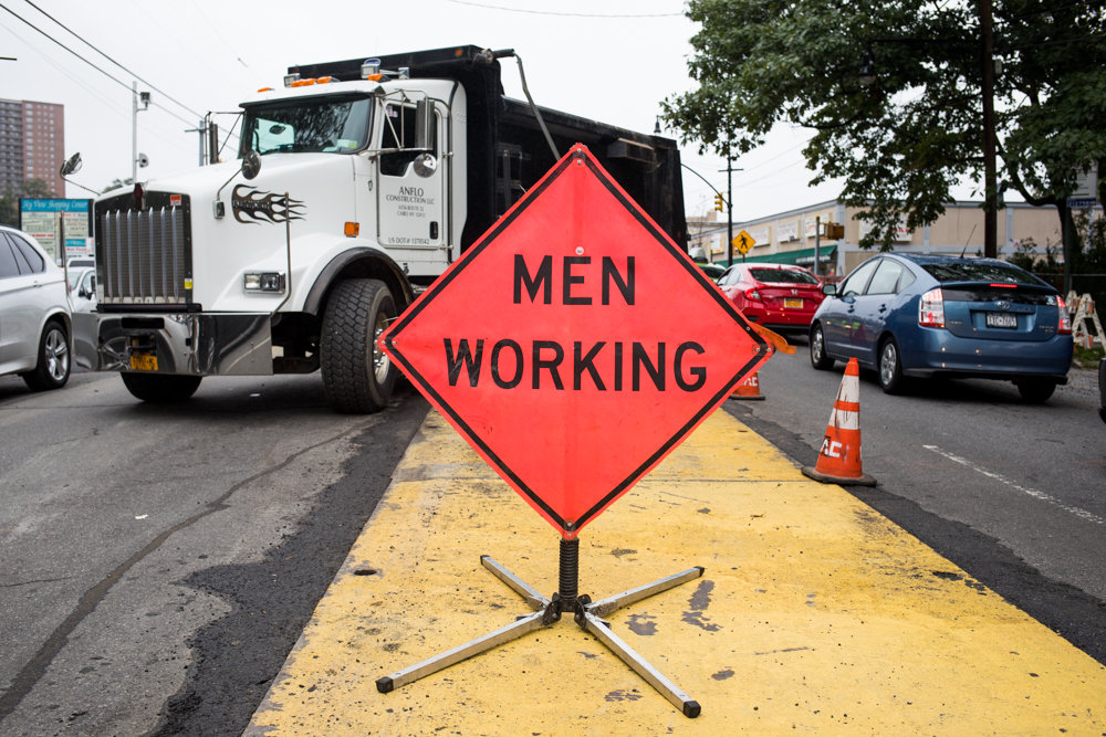 A 'men working' sign posted on Riverdale Avenue indicates ongoing gas line repair work that has created a traffic bottleneck and caused a significant number of headaches. The subsequent repairs are a result of disorganized planning on the city transportation department's part when it comes it issuing street work permits closely together.