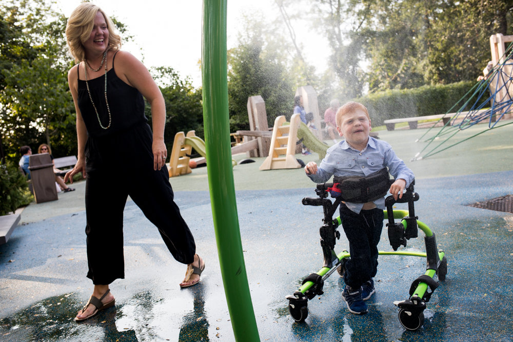 Benjamin Klein-Foglio walks through the sprinkler with his mother, Jessica, at Skyview-on-the-Hudson's playground. Benjamin, 3, has Salla disease, a rare affliction that causes physical and intellectual impairments. His mother has created a nonprofit called the Star Foundation to help children like her son.