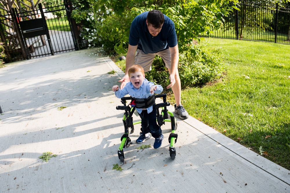 Benjamin Klein-Foglio walks with the help of his father, Michael, at Skyview-on-the-Hudson's playground. The 3-year-old has Salla disease, prompting his mother Jessica to build the Star Foundation, a nonprofit dedicated to research on the rare condition.