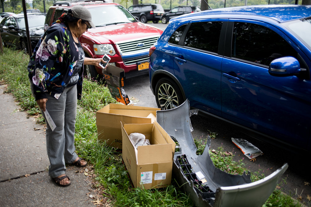 Cruz Inaru Pastrano tosses a piece of garbage back into the box where she found it next to a vehicle bumper along Washington's Walk, south of the Jerome Park Reservoir. Car owners often work on their vehicles in the area, Pastrano says, leaving garbage on the street.