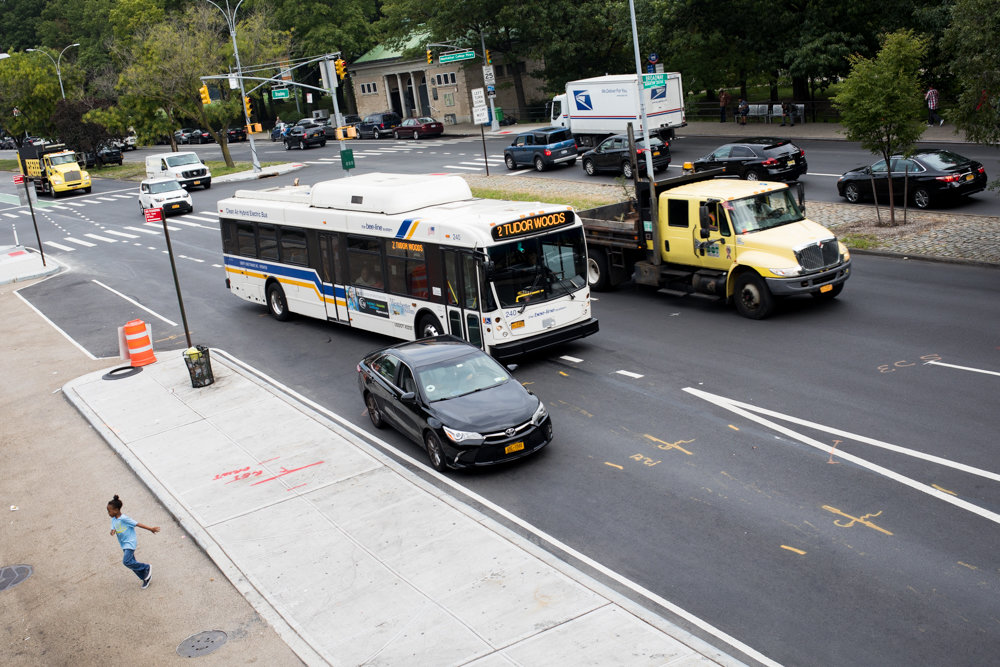A Bee-Line bus from Westchester County navigates around a stopped car at a bus bulb located on the southbound side of Broadway near West 242nd Street. Nearby merchants have complained about the traffic problems this newly installed bulb causes.