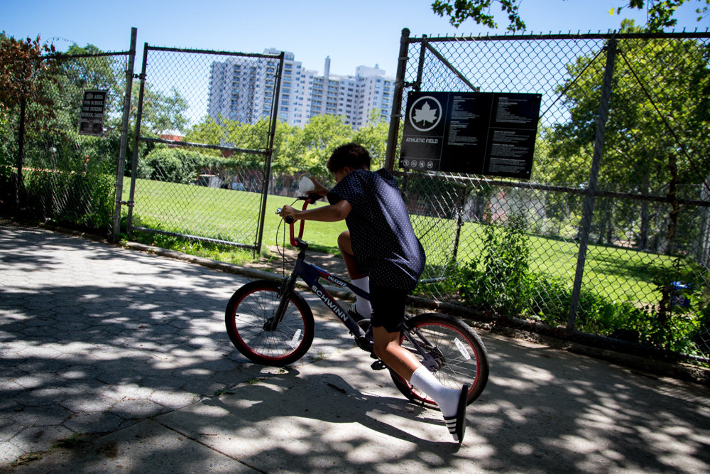 A kid zooms on his bicycle near Riverdale Playground.