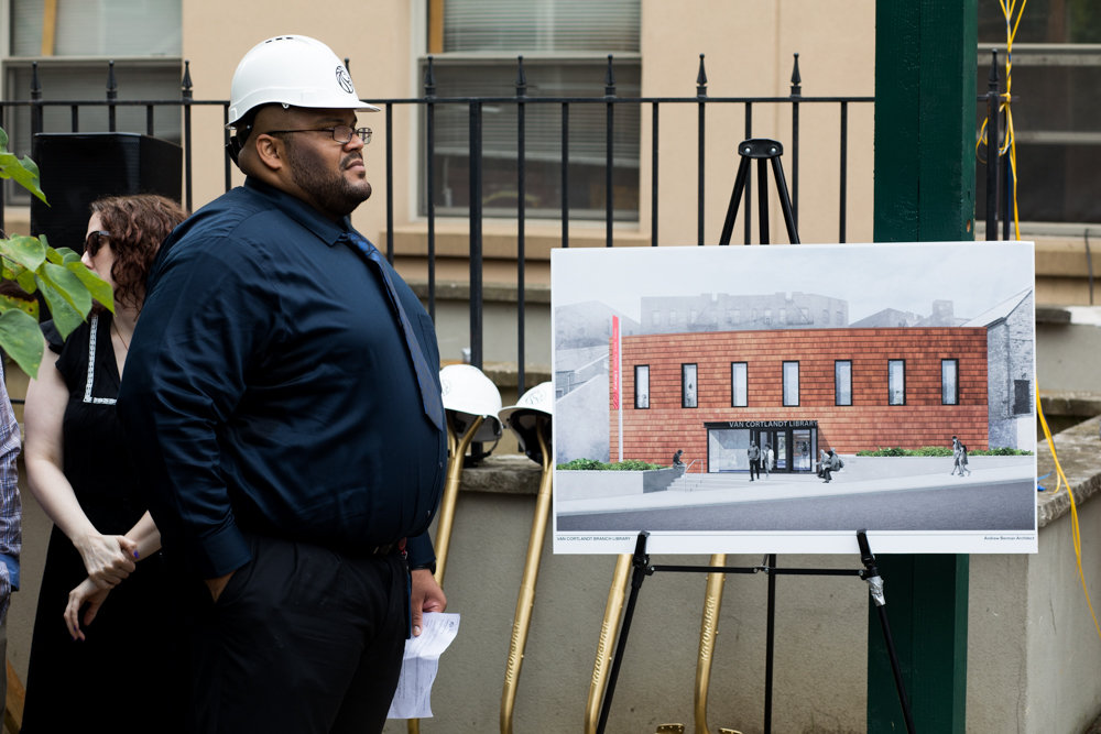 Peter Pamphile, manager of the Van Cortlandt Library, stands next to a rendering of the library's new location at 3882 Cannon Place during opening remarks at a groundbreaking ceremony. The new library is expected to be completed next summer.