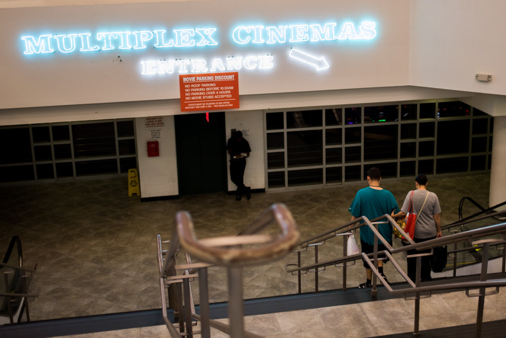 People head downstairs to the movies at Concourse Plaza Multiplex Cinemas near Yankee Stadium, one of only two movie theaters in the Bronx.