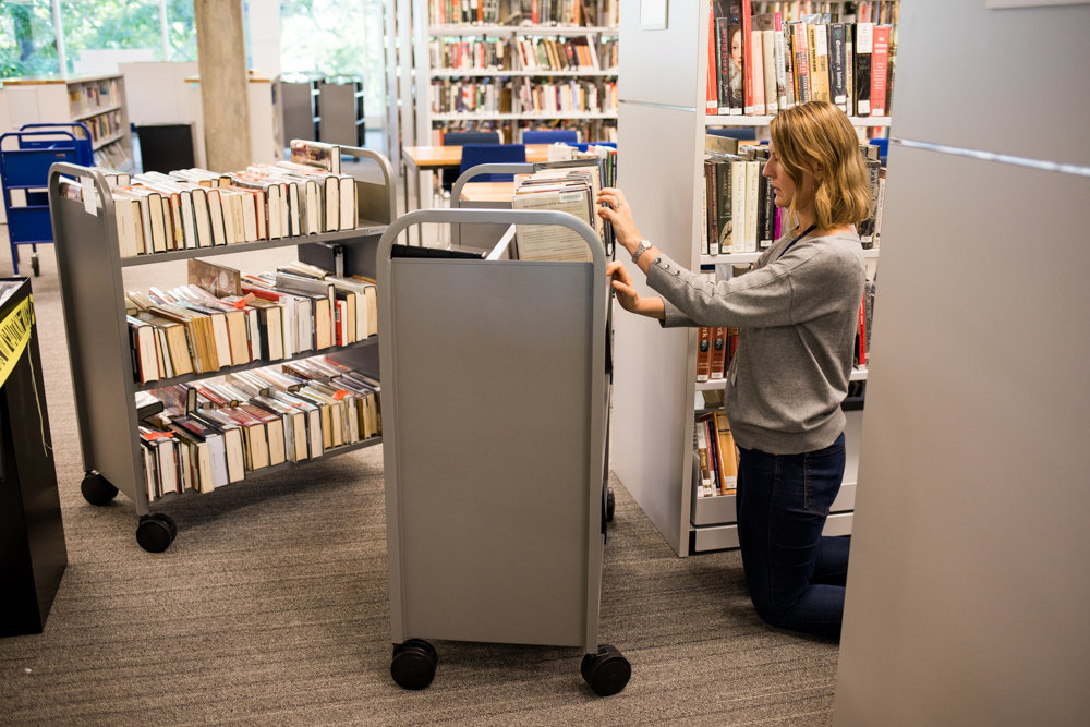 Katie Elwood, a librarian at Ethical Culture Fieldston School, organizes books in the school's newly redesigned library. Renovations took 16 months, and cost $16 million.