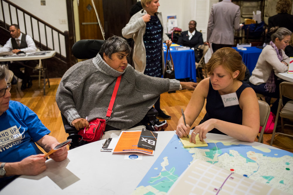 Iffat Mahmud-Khan participates in an MTA workshop where commuters were encouraged to share their concerns about and suggestions for the bus system. Using stickers and maps of the Bronx, commuters were able to locate their routes and the places where problems occurred for them.