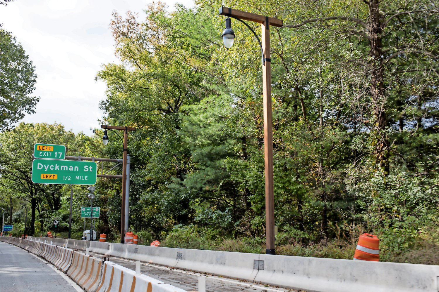Wooden lampposts line the southbound side of the Henry Hudson Parkway in Manhattan. The transportation department is installing wooden lampposts along the parkway and the bridge as a sustainability measure.