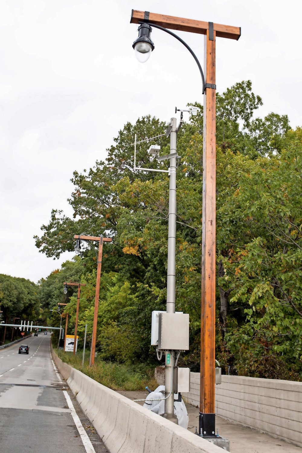 Wooden lampposts line the northbound side of the Henry Hudson Parkway in Manhattan. The transportation department is installing wooden lampposts along the parkway and the bridge as a sustainability measure.