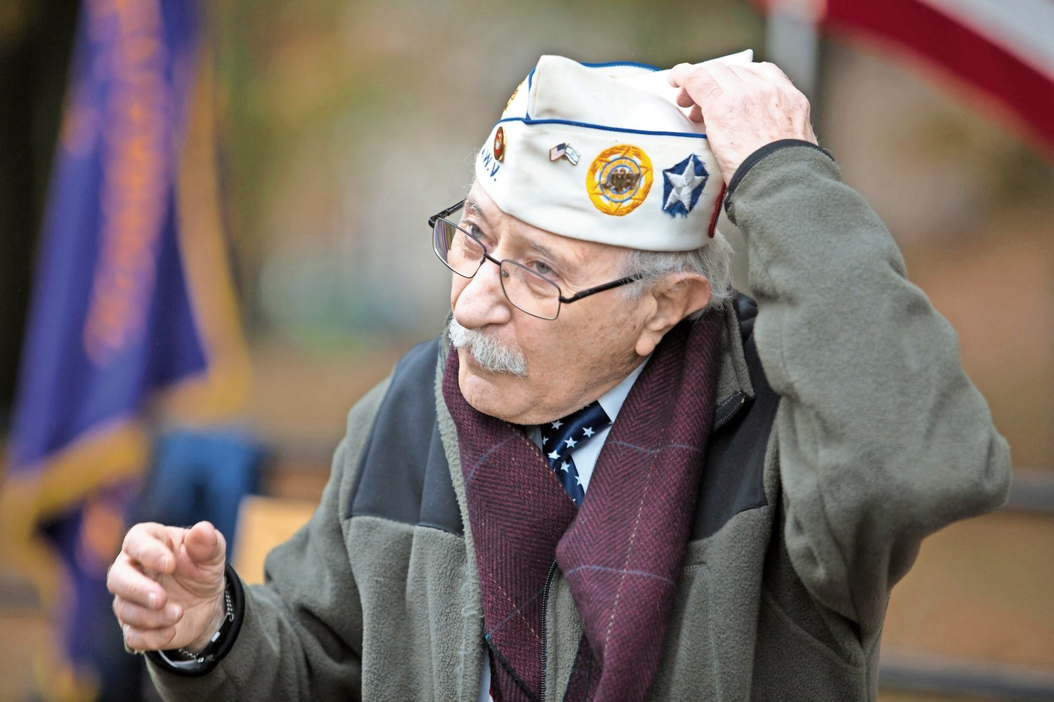 Herb Barrett puts on his cap before opening the Veterans Day ceremony at Van Cortlandt Park's Memorial Grove last year. Barrett first organized the ceremony in 2007 with his friend and fellow veteran Donald Tannen, who passed away in 2014.
