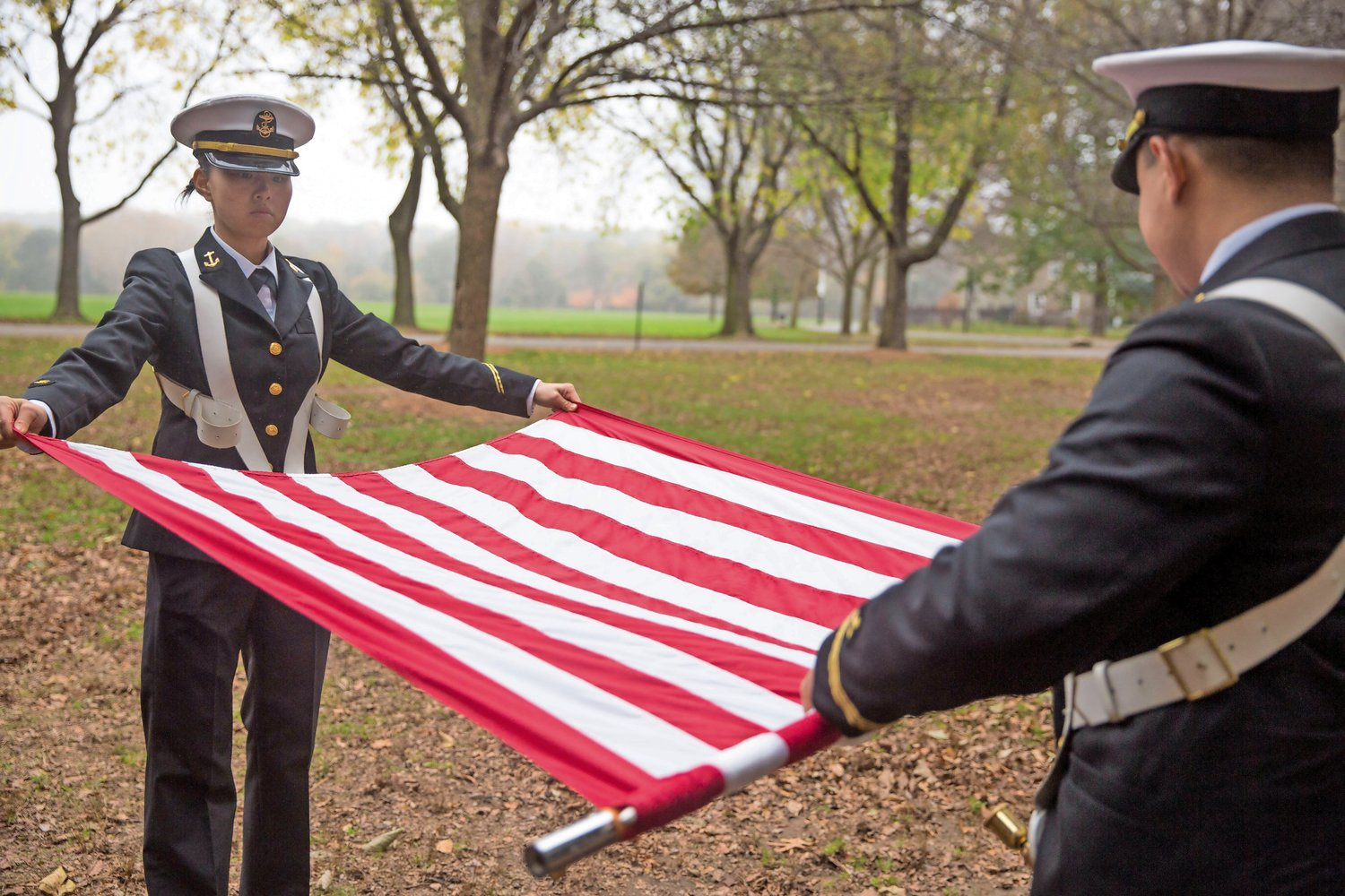 Members of the SUNY Maritime College Color Guard roll the flags after the presentation of colors at a Veterans Day ceremony at Memorial Grove last year.