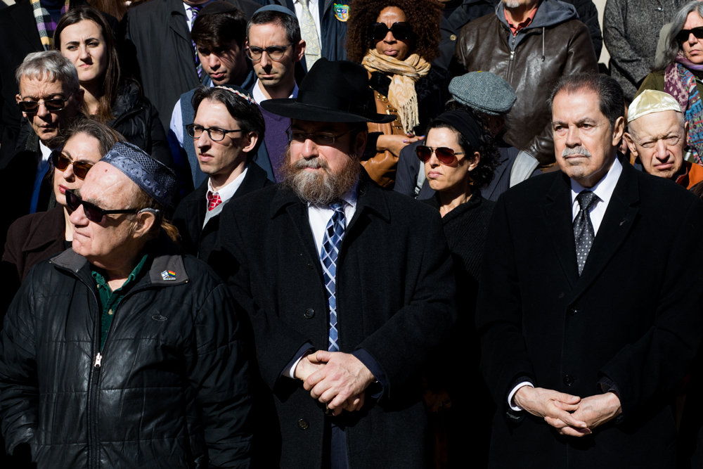 Community members, religious leaders and elected officials — including Rabbi Levi Shemtov, center, and U.S. Rep. José Serrano, right — stand at a prayer vigil for the victims of the mass shooting at the Tree of Life Synagogue in Pittsburgh.
