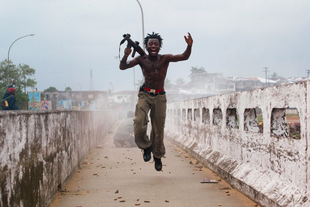 Joseph Duo, a Liberian militia commander loyal to the government, exults after firing a rocket-propelled grenade at rebel forces at a key strategic bridge July 2003. This image is included in the exhibition 'War and Peace in Liberia' at the Bronx Documentary Center, on display through Dec. 16.