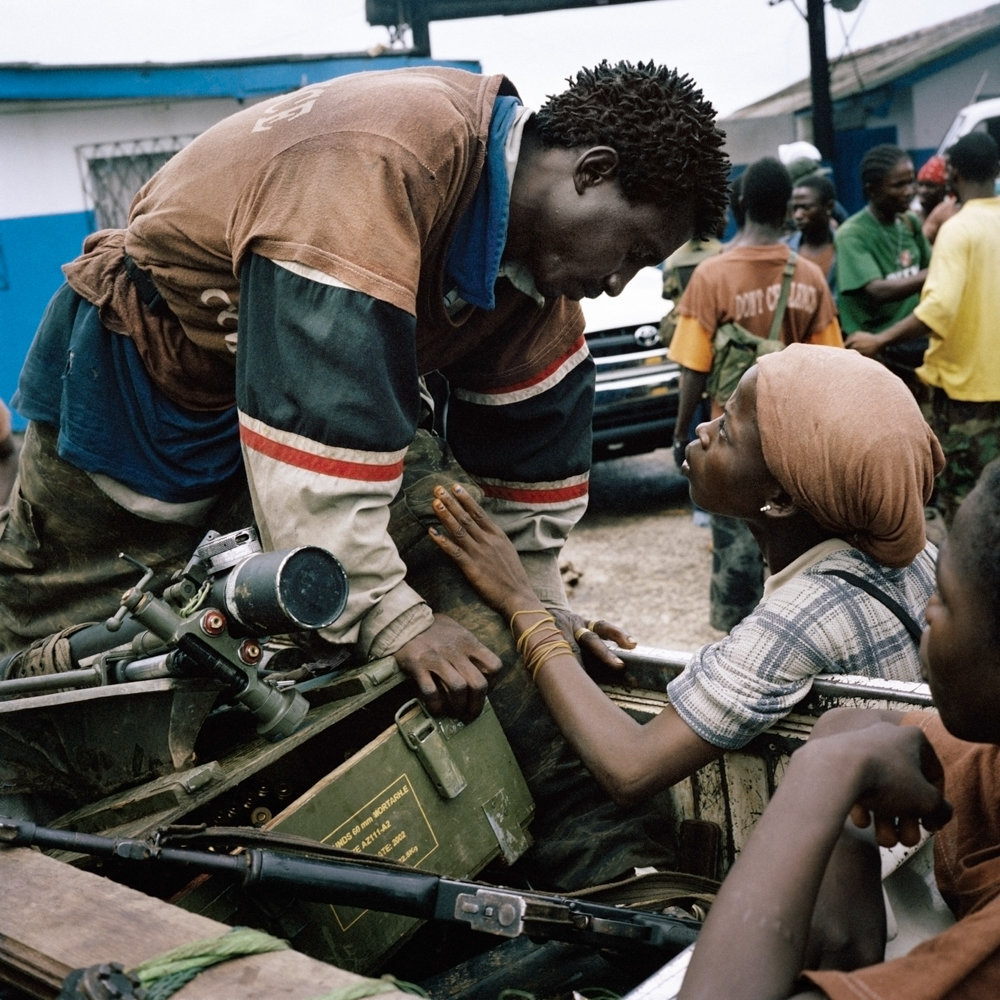 A member of the anti-aircraft brigade exchanges a brief tender word with his girlfriend during heavy fighting in the Liberian capital of Monrovia.