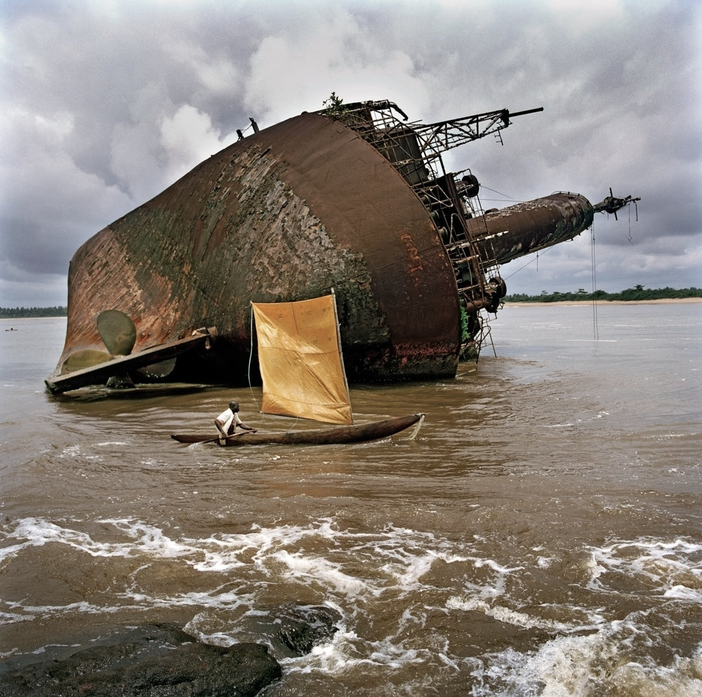 A fisherman passes the wreck of an old ship off the port of Greenville, Liberia, in 2005. Tim Hetherington moved to Liberia after a civil war ended in 2003, and lived there for several years where he photographed the country's road to recovery.
