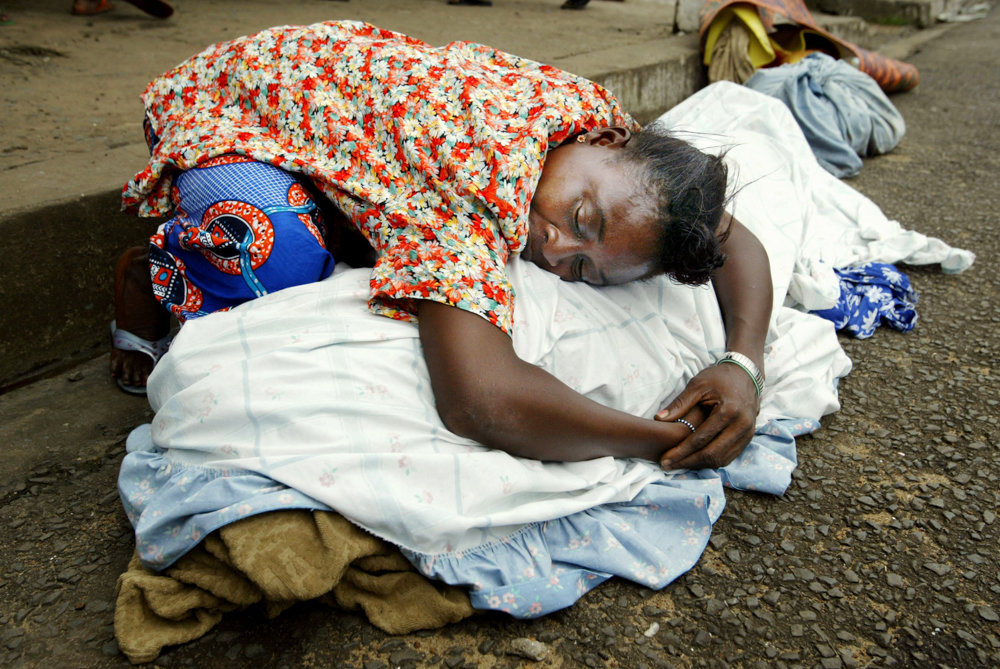 A woman grieves over the body of a relative outside a church in Monrovia, Liberia, in 2003. This image is included in the exhibition 'War and Peace in Liberia' at the Bronx Documentary Center, which is on display through Dec. 16.