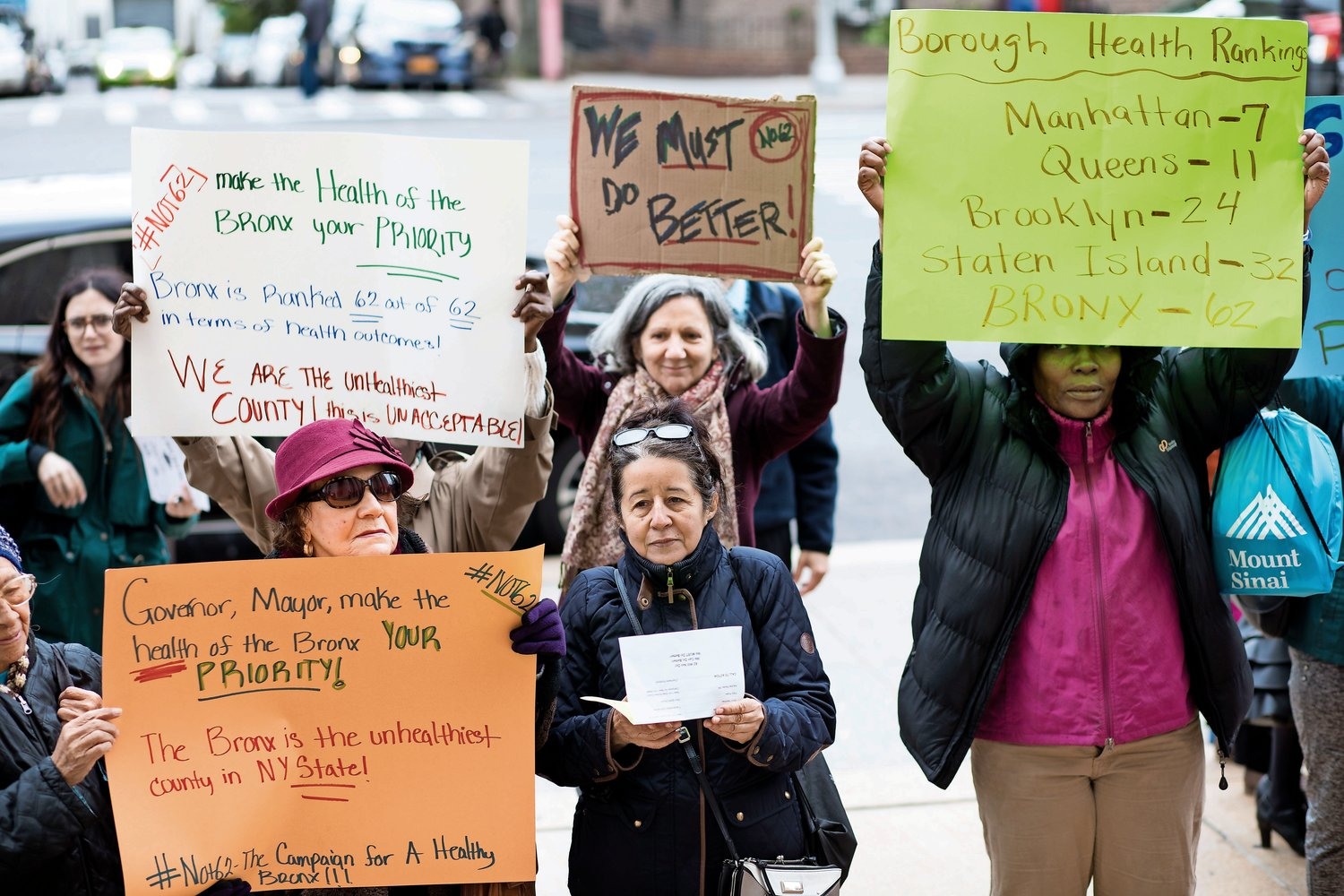 People hold signs at a rally highlighting the fact that the Bronx ranks last in the County Health Rankings and Roadmaps Report, a joint effort by the University of Wisconsin and the Robert Wood Johnson Foundation to measure how health is influenced by where live.