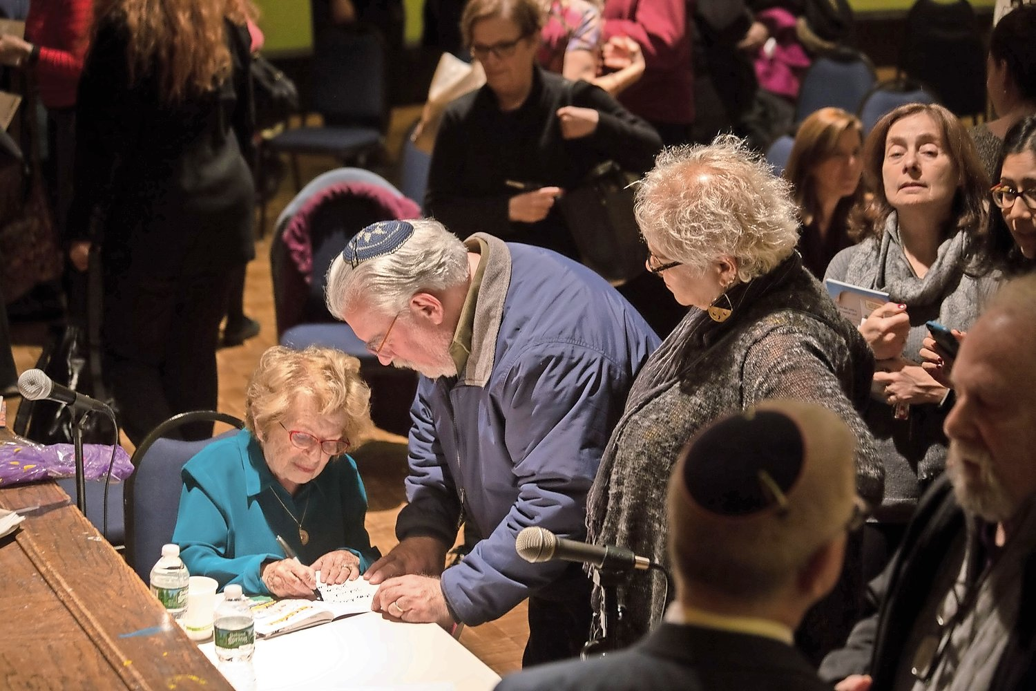 Dr. Ruth Westheimer signs one of her books for an audience member after her talk at the Conservative Synagogue Adath Israel of Riverdale.