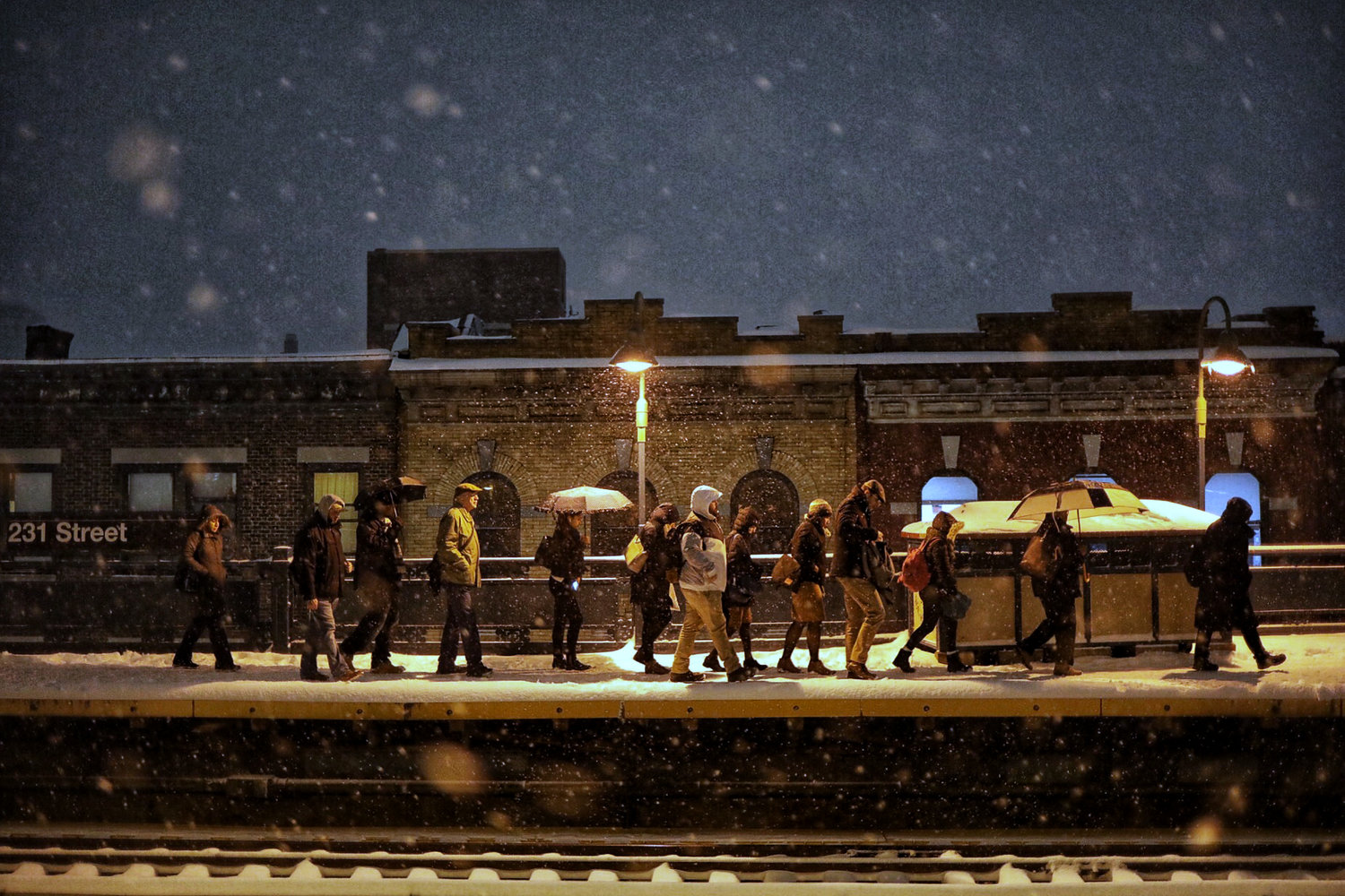 Commuters trudge through the snow toward the stairs after disembarking from an uptown 1 train at the 231st Street stop.