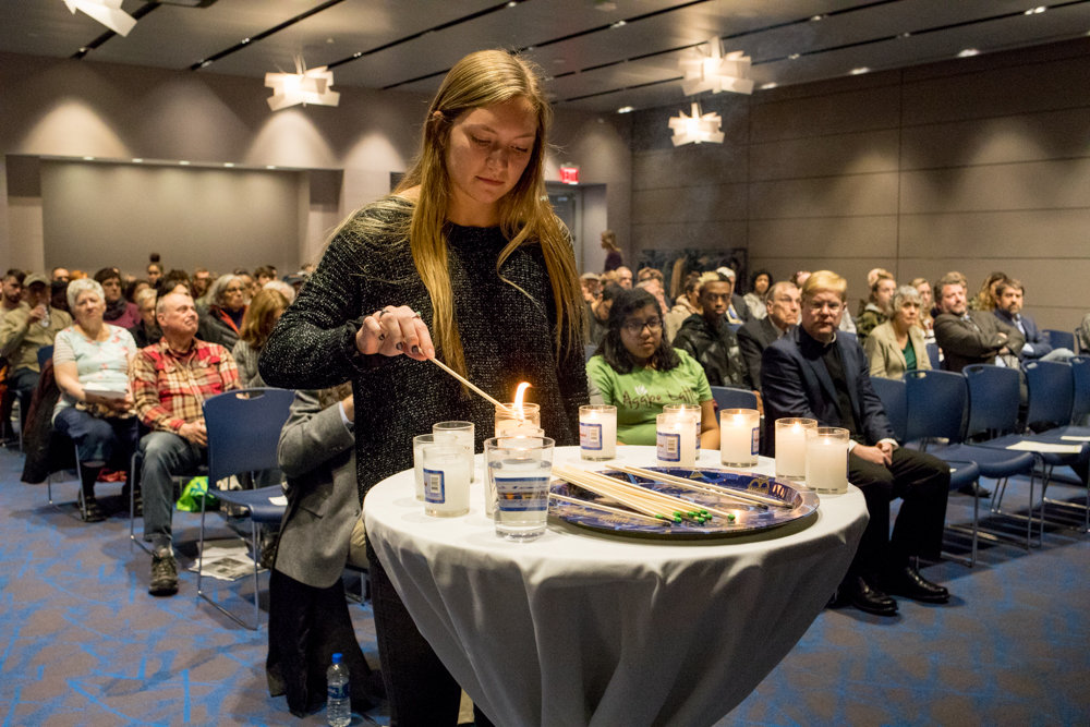 Allyson Oertel lights a candle for Simon Sylvan, a victim of the mass shooting at the Tree of Life Synagogue in Pittsburgh, at a Manhattan College remembrance of Kristallnacht, a 1938 pogrom against Jews during World War II.