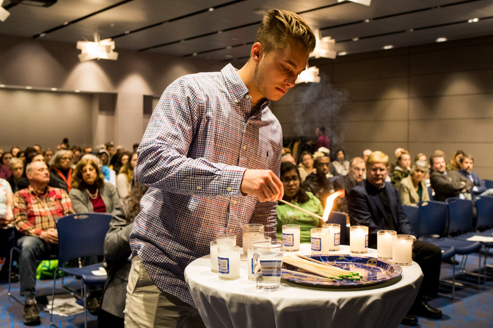 Joseph Mattone lights a candle for David Rosenthal, a victim of the mass shooting at the Tree of Life Synagogue in Pittsburgh, at a Manhattan College remembrance of Kristallnacht, a 1938 pogrom against Jews during World War II.