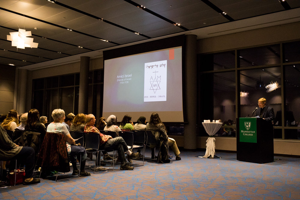 Kevin Spicer, a professor of history at Stonehill College, speaks about his new book at a Manhattan College remembrance of Kristallnacht, a 1938 pogrom against Jews during World War II in 1938.