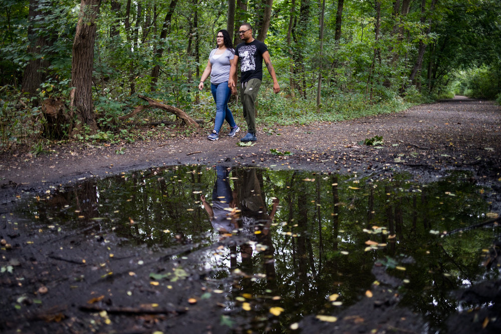 Toni Seguinot and Adam Woodley walk alongside a puddle on the Old Putnam Trail in Van Cortlandt Park. A plan is in place — and funding secured — to pave a portion of the trail extending from the northern region of the park to the bottom of Van Cortlandt Lake. But both Seguinot and Woodley, who walk the trail at least once a week, feel it would diminish the park's natural beauty.