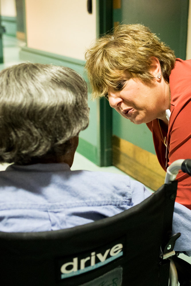 Franca Martino-Starvaggi speaks with a patient at the Schervier Nursing and Rehabilitation Center. Martino-Starvaggi is the director of social work, helping patients and their families emotionally and socially to combat illnesses and loss.