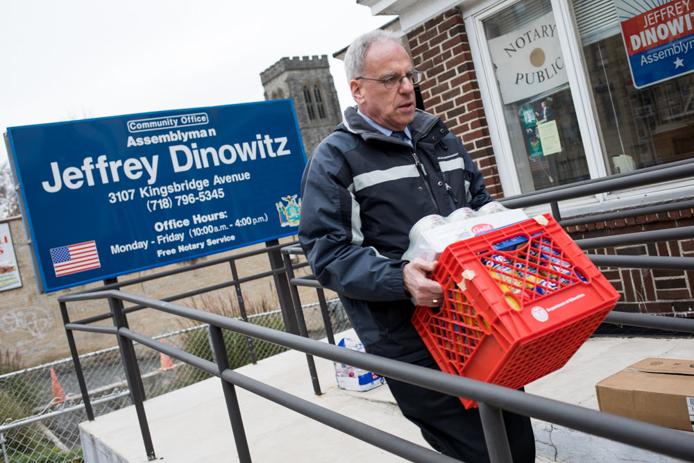 Assemblyman Jeffrey Dinowitz carries a milk crate filled with canned food to a car parked outside his office. Dinowitz's office has collected a wide array of packaged food as part of its annual holiday canned food drive that will donate the food to the Kingsbridge Heights Community Center and the Saint Francis of Rome Food Pantry.