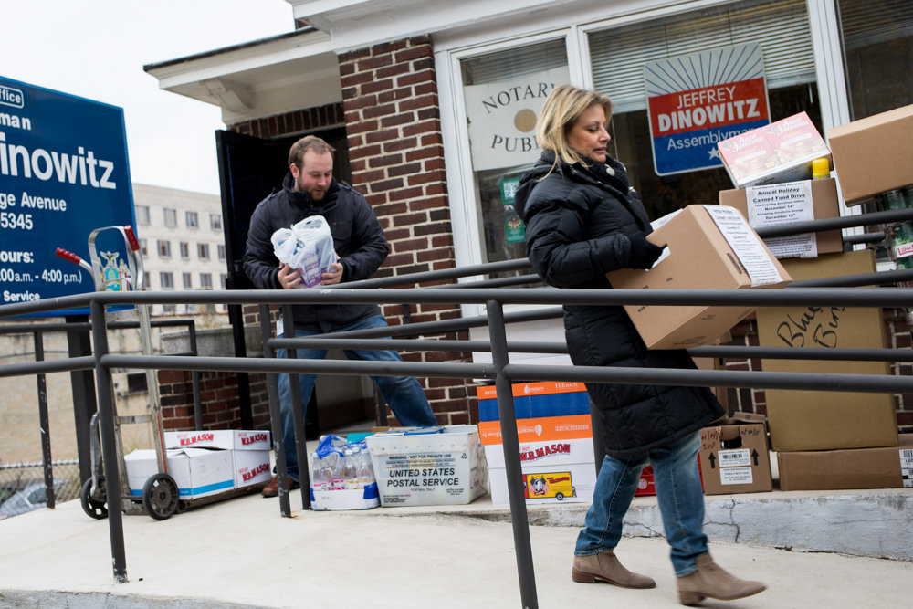 Randi Martos, chief of staff for Assemblyman Jeffrey Dinowitz, right, carries a box of packaged food while Ivan Nedds, Dinowitz's community liaison, assembles boxes of packaged food on a hand truck. The donated food is part of Dinowitz's annual holiday canned food drive, earmarked for the Kingsbridge Heights Community Center and the Saint Francis of Rome Food Pantry.