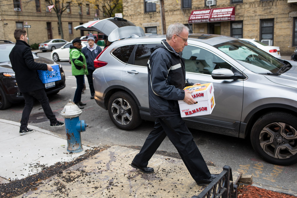 Assemblyman Jeffrey Dinowitz carries a box filled with canned food to a car. Dinowitz's office has collected a wide array of packaged food as part of its annual holiday canned food drive for the Kingsbridge Heights Community Center and the Saint Francis of Rome Food Pantry.